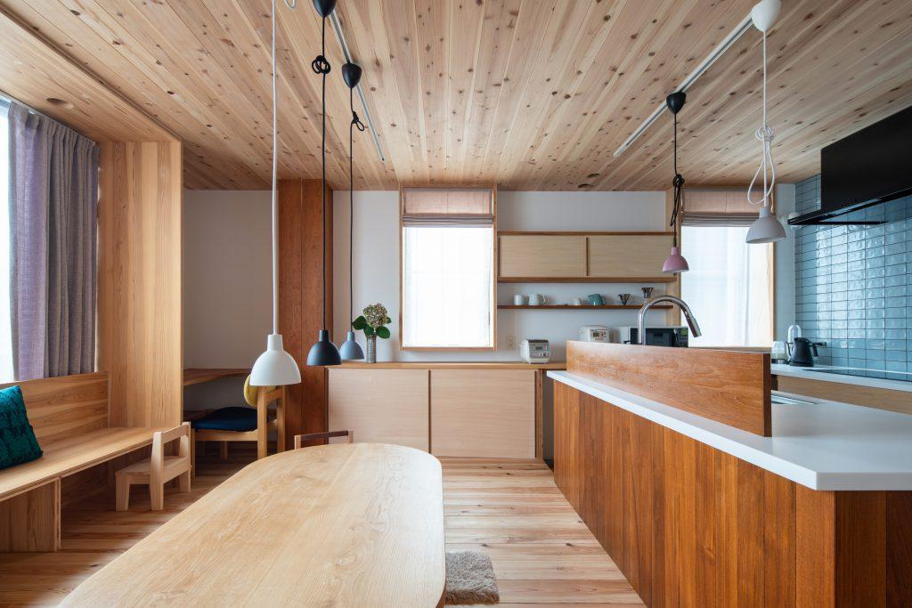 住まいの中心であるLDK。窓際には造り付けベンチを設置し、キッチンに立つ人とのコミュニケーションが図り易くなるように配慮している。目線が合うようにダイニングテーブルゾーンよりキッチン側は床を15㎝下げて作っている。